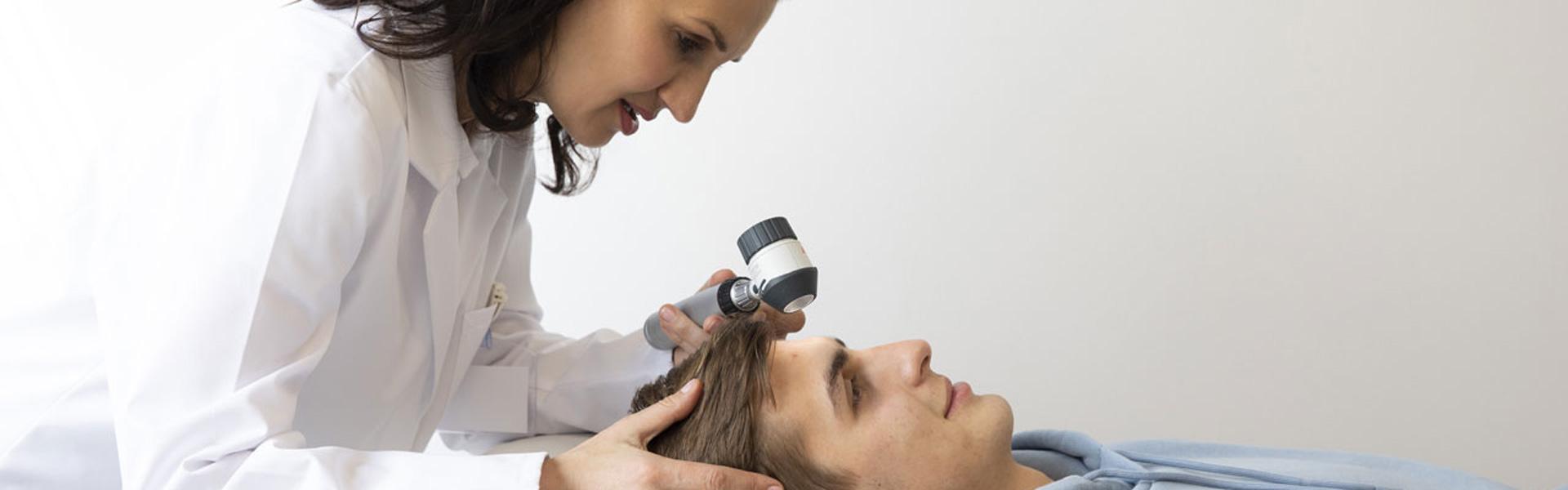 Dermatologinja z dermatoskopom pregleduje pacienta
